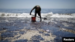 William McConnaughey, 56, who drove from San Diego to help shovel oil off the beach, stands in an oil slick in bare feet along the coast of Refugio State Beach in Goleta, California, United States, May 20, 2015. A pipeline ruptured along the scenic Califo