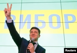 Ukrainian comic actor and presidential candidate Volodymyr Zelenskiy flashes a victory sign following the announcement of the first exit poll in a presidential election at his campaign headquarters in Kyiv, March 31, 2019.