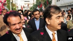 Pakistan's Prime Minister Yousuf Raza Gilani (R) and Interior minister Rehman Malik (L) arrive at the Muttahida Qaumi Movement (MQM) headquarters in Karachi, Jan 7, 2011.