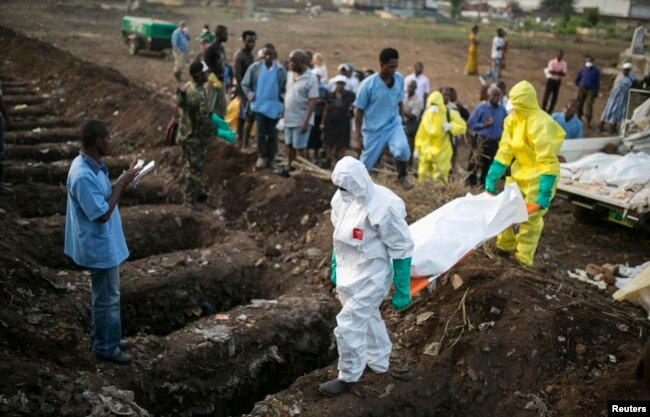 FILE - Health workers carry the body of an Ebola victim for burial at a cemetery in Freetown, Dec. 17, 2014.