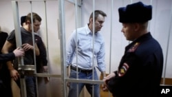 Russian opposition activist and anti-corruption crusader Alexei Navalny, 38, second right, and his brother Oleg Navalny, left, enter into the cage at a court in Moscow, Dec. 30, 2014.