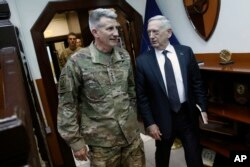 FILE - U.S. Defense Secretary James Mattis, right, and U.S. Army General John Nicholson, commander of U.S. Forces Afghanistan, arrive to meet with an Afghan defense delegation at Resolute Support headquarters, in Kabul Afghanistan, April 24, 2017.