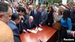El gobernador de California Jerry Brown rodeado por los patrocinadores de la legislación promulga la nueva ley que otorgará licencias de conducir a indocumentados.