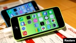 FILE - These then-new Apple iPhone 5c models were on display in at Tokyo store on Sept. 20, 2013. A 5c is at the center of Apple's battle with the FBI over efforts to break the company's proprietary auto-destruct security system.