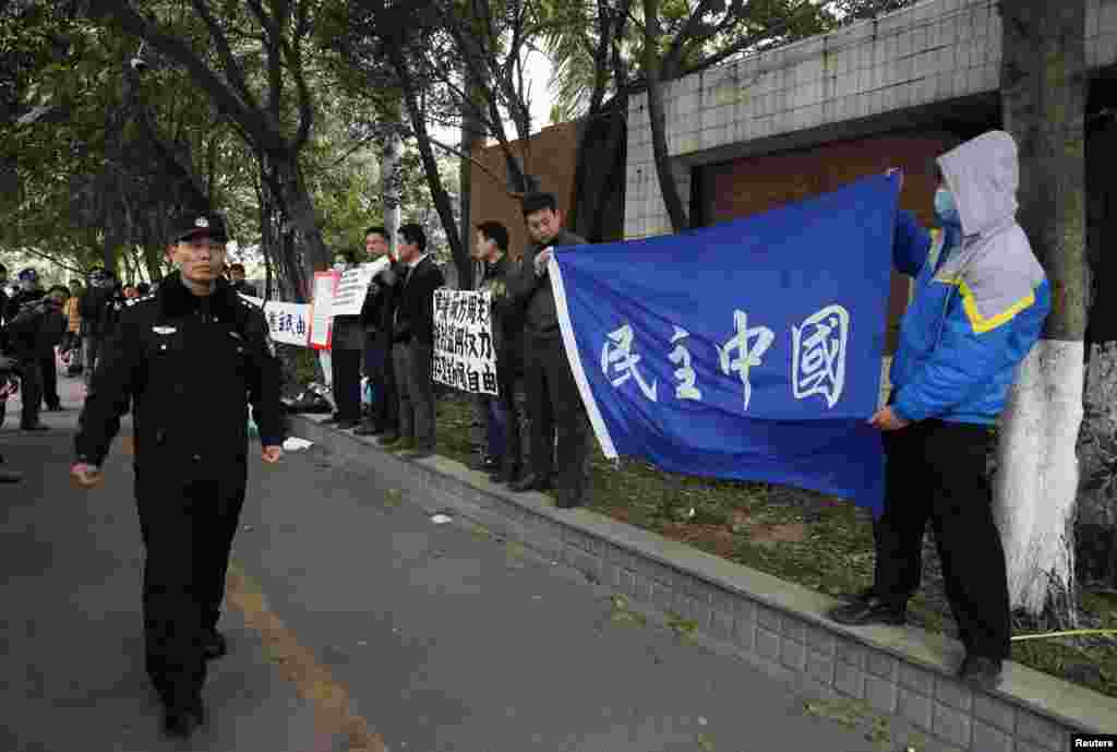 A police officer walks past supporters of Southern Weekly demonstrating outside the office of the liberal newspaper in the southern Chinese city of Guangzhou, January 9, 2013.