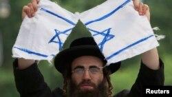 Seorang umat Yahudi Ortodoks anti-Zionis menyobek bendera Israel dalam protes melawan negara Israel di New York.