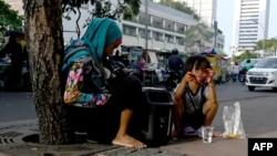 Seorang anak bersama neneknya beristirahat di jalur pejalan kaki di Jakarta, 10 Oktober 2019. Maraknya makanan murah dan mengenyangkan, tapi minim gizi mengakibatkan jutaan anak mengalami masalah kesehatan. (Foto: AFP)