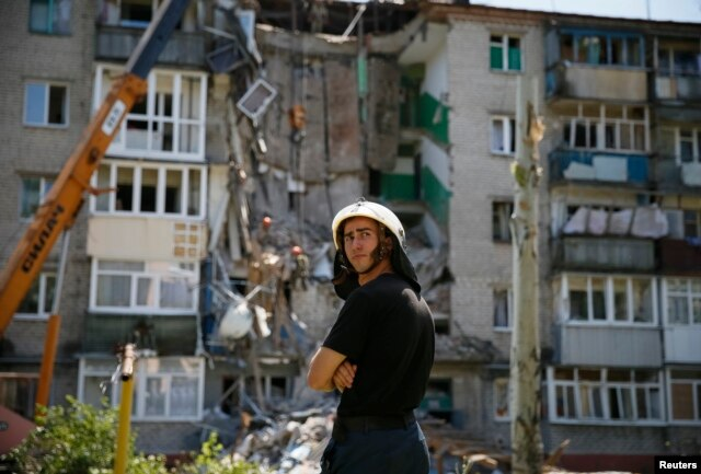 A rescuer stands near a shattered five-storey building, which was damaged by a recent shelling, in the eastern Ukrainian town of Slaviansk July 16, 2014.