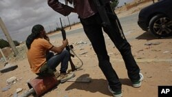 Libyan rebel fighters wait at a staging area near the village of Shal Ghouda in western Libya, August 11, 2011