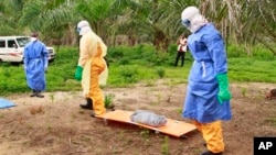 The wrapped remains of a new born child suspected of contracting the Ebola virus, lays on a stretcher as health workers, dressed in Ebola protective gear, move the body for burial in Dubreka, Guinea, Jan. 19, 2017.