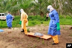 FILE - In this photo taken on Friday, June 19, 2015, the wrapped remains of a new born child suspected of contracting the Ebola virus, lays on a stretcher as health workers, dressed in Ebola protective gear, move the body for burial in Dubreka, Guinea.