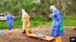 Dans cette photo prise le vendredi 19 Juin, 2015, les restes enveloppés d'un nouveau-né soupçonné d'avoir contracté le virus Ebola, allongés sur une civière que les travailleurs de la santé transportent pour l'enterrement à Dubreka, en Guinée.