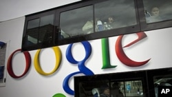 FILE - Passengers look through windows on a bus painted with an advertisement for Google in Beijing, China.