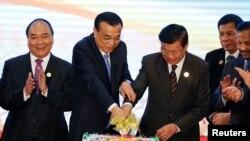 리커창(왼쪽 두번째) 중국 총리가 7일 라오스 수도 비젠티안의 동남아시아국가연합(아세안) 정상회의 현장에서 통룬 시술릿 라오스 총리와 함께 케이크를 자르고 있다.