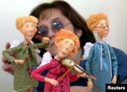 """Seorang karyawan galeri mengatur komposisi boneka """"Angels"""" dalam persiapan pameran boneka tangan di Moskow, 10 Desember 2003. (Foto: REUTERS). Pameran ini kembali digelar di Moskow tahun ini."""