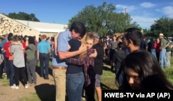 FILE: In this image made from a video by KWES-TV, people gather near the Alpine High School school campus after a shooting, in Alpine, Texas, Thursday, Sept. 8, 2016.