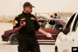 FILE - An Iraqi counter terror officer talks to people in a convoy of families fleeing Islamic State-held Hit, Iraq, at a checkpoint on the western edge of Ramadi, Iraq, March 20, 2016.