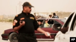 An Iraqi counterterror officer talks to people in a convoy of families fleeing Islamic State-held Hit, Iraq, at a checkpoint on the western edge of Ramadi, Iraq, March 20, 2016.