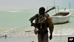 A Somali, part armed militia, part pirate, carries his high-caliber weapon on a beach in the central Somali town of Hobyo on Aug. 20, 2010.