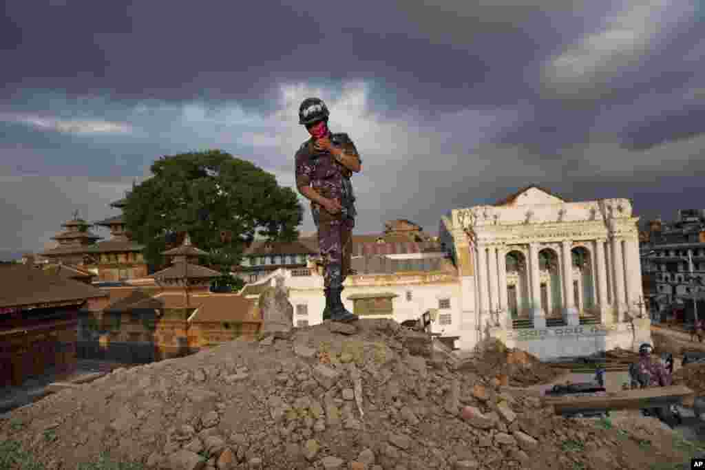 A Nepalese policeman stands atop of a rubble at Basantapur Durbar Square that was damaged in Saturday's earthquake in Kathmandu, Nepal.