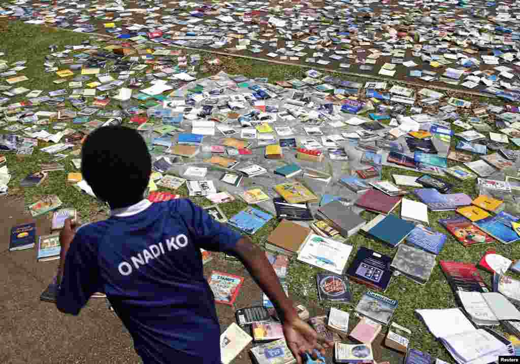 A boy runs past books laid to dry in the sun after the roof of the Central School library was blown away by Cyclone Pam in Port Vila, the capital city of the Pacific island nation of Vanuatu, March 18, 2015.