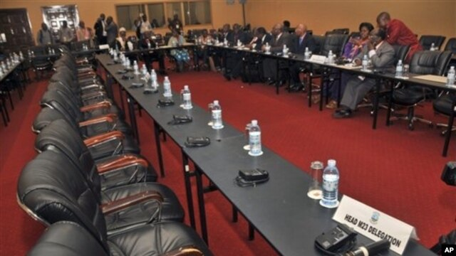 Congolese delegation sits opposite row of empty seats intended for delegation of M23 rebels, Kampala, Uganda, Dec. 10, 2012.