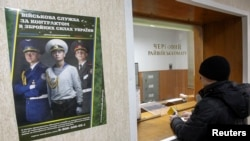 A man stands in front of a counter's window at a district army recruiting office in Kyiv, Ukraine, March 2, 2014.