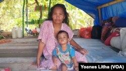 Besaria dan anak balitanya berusia tiga tahun di salah satu tenda terpal di dusun Petakeang, Kecamatan Tapalang, Sulawesi Barat. Jumat (5/1/2021). (Foto: VOA/Yoanes Litha)