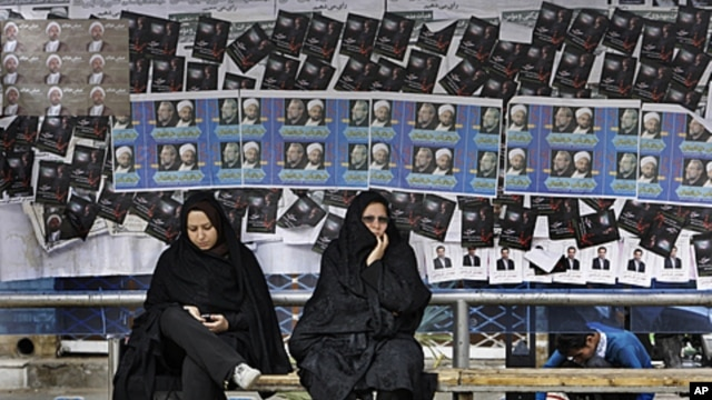 Iranian women sit at bus stop, in front of parliamentary elections campaign posters in the city of Qom, 78 miles (125 kilometers) south of the capital Tehran, March 1, 2012.