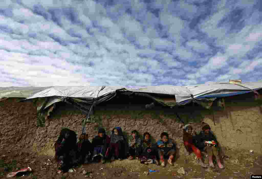 Internally displaced Afghan children sit near their shelter at a refugee camp in Kabul, Afghanistan, January 19, 2013.