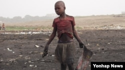 가나 아그보그블로 시에서 어린이가 전자제품 폐기물이 타고 남은 잿더미에서 금속 조각을 찾고 있다.