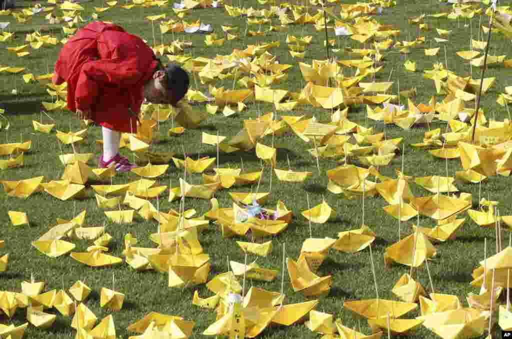 A girl reads massages written on paper ships for the victims of the sunken ferry Sewol at a group memorial altar in Seoul, South Korea.