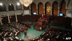 FILE - Tunisian Prime Minister Youssef Chahed addresses parliament during a session in Tunis, March 23, 2018.