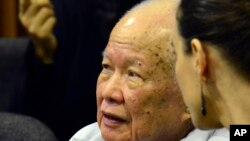 In this photo released by the Extraordinary Chambers in the Courts of Cambodia, Khieu Samphan, left, former Khmer Rouge head of state, sits in the court room during a hearing at the U.N.-backed war crimes tribunal, in Phnom Penh, Cambodia, Oct. 17, 2014.