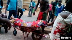 Seorang korban serangan bom dilarikan di atas gerobak di pasar Jos, 20/5/2014. Rentetan bom menewaskan lebih dari 100 orang di kota Jos. Nigeria.