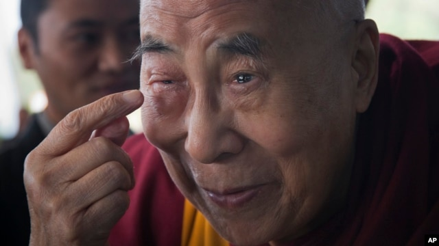 Tibetan spiritual leader the Dalai Lama points to his swollen right eye as he talks to journalists before boarding his chartered flight in Dharmsala, India, Jan. 19, 2016.