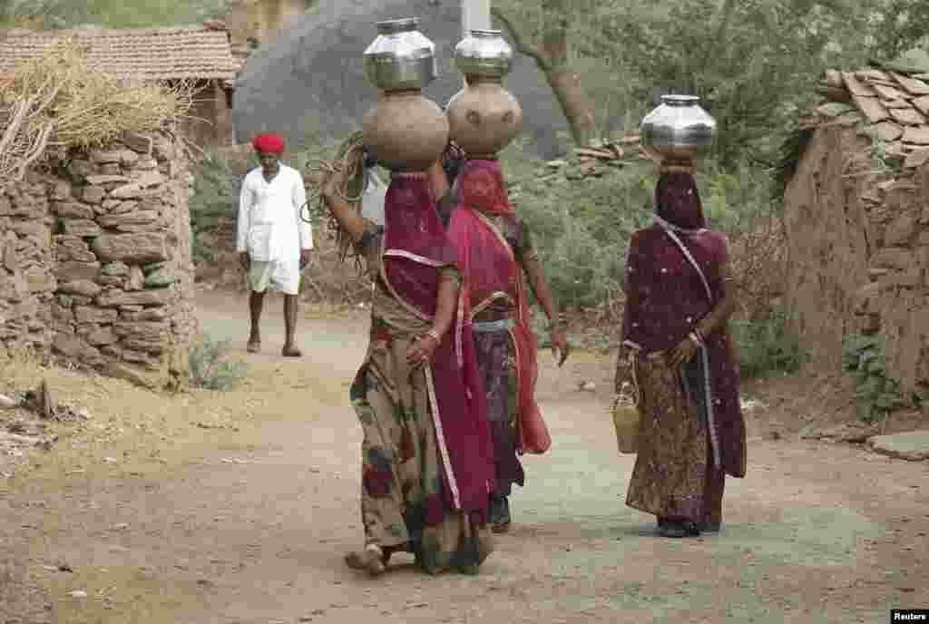 Những người phụ nữ đội các bình chứa đầy nước uống trong làng Devmali ở bang hoang mạc Rajasthan của Ấn Độ.