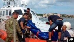 Para penjaga pantai mengangkat jenazah migran yang menjadi korban kapal terbalik di pelabuhan Pulau Lampedusa, Italia (3/10).