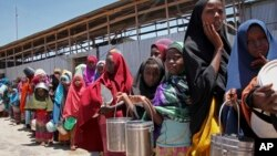 FILE - Displaced Somali girls who fled the drought in southern Somalia stand in a queue to receive food handouts at a feeding center in a camp in Mogadishu, Somalia, Feb. 25, 2017.