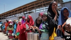 FILE - Displaced Somali girls who fled the drought in southern Somalia stand in a queue to receive food handouts at a feeding center in a camp in Mogadishu, Feb. 25, 2017.