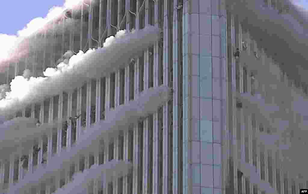 Jahon Savdo Markazining Shimoliy binosi derazalarida osilib turgan odamlar.2001-yil, 11-sentabr. Nyu-York, AQSh.