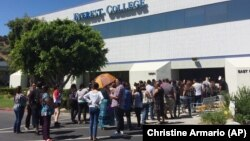 FILE - Students wait outside Everest College in Industry, California after it shut down all of its remaining 28 ground campuses in April 2015.