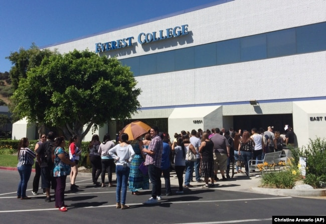 FILE - Students wait outside Everest College in Industry, California after it shut down all of its remaining 28 ground campuses in April 2015. The shutdown came after the U.S. Department of Education announced it was fining the for-profit institution.