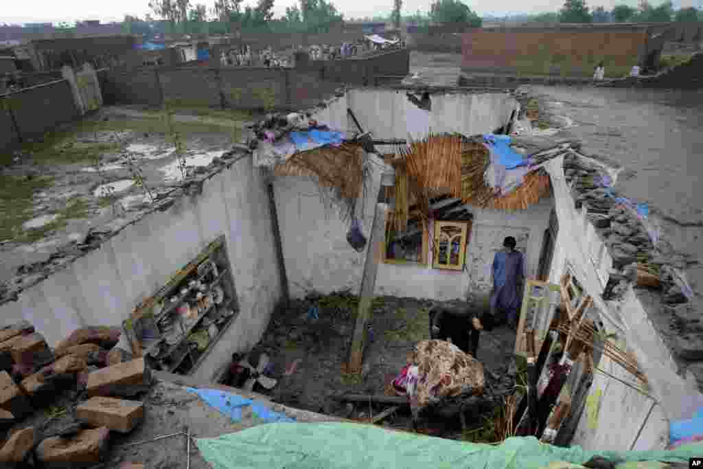 People collect their belongings from a house damaged from heavy rain and windstorms Sunday evening in Peshawar, Pakistan.