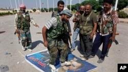 Chiến binh phe Quân đội Syria Tự do dẫm chân lên bức hình chân dung của Tổng thống Syria Bashar Assad, ngày 22/9/2012.