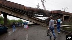 People walk under a destroyed railroad bridge over a main road leading into Donetsk, near the village of Novobakhmutivka, north of Donetsk, eastern Ukraine, July 7, 2014.