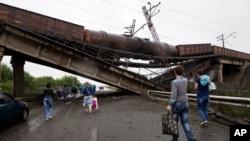 Warga berjalan di bawah jembatan kereta api yang runtuh ke jalan utama menuju Donetsk, Ukraina timur (7/7).