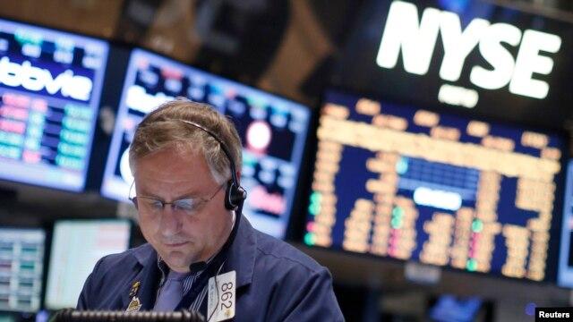 Seorang pekerja tengah mengamati perkembangan saham di lantai bursa New York (NYSE), 15 February 2013. (REUTERS/Brendan McDermid).