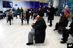 FILE - People wait at the reception hall of a COVID-19 vaccination mega center in Athens, Feb. 15, 2021.