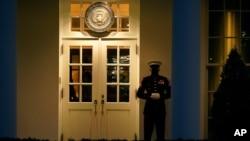 Marinac stoji na ulazu u zapadno krilo Bele kuće, nakon što je Predstavnički dom opozvao predsednika Donalda Trampa 13. januara 2021. Prisustvo čuvara znači da se predsednik nalazi u Ovalnoj kancelariji.